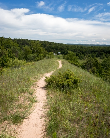 The trail circles back along a steep dune to the old Treat Farm in the distance.